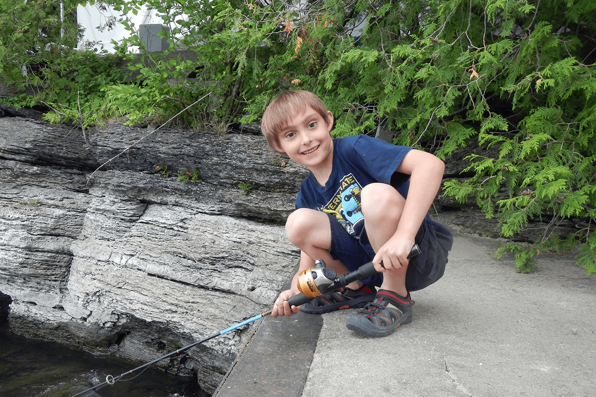 Image of boy with a fishing rod. LAC Summer Camps.