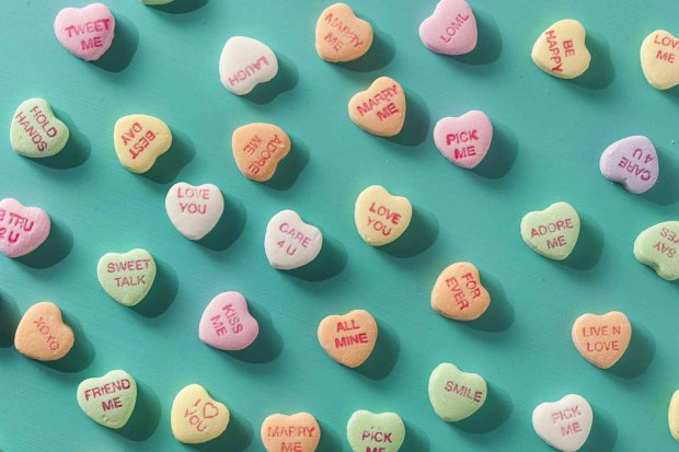 Candy Conversation Hearts arranged on teal background