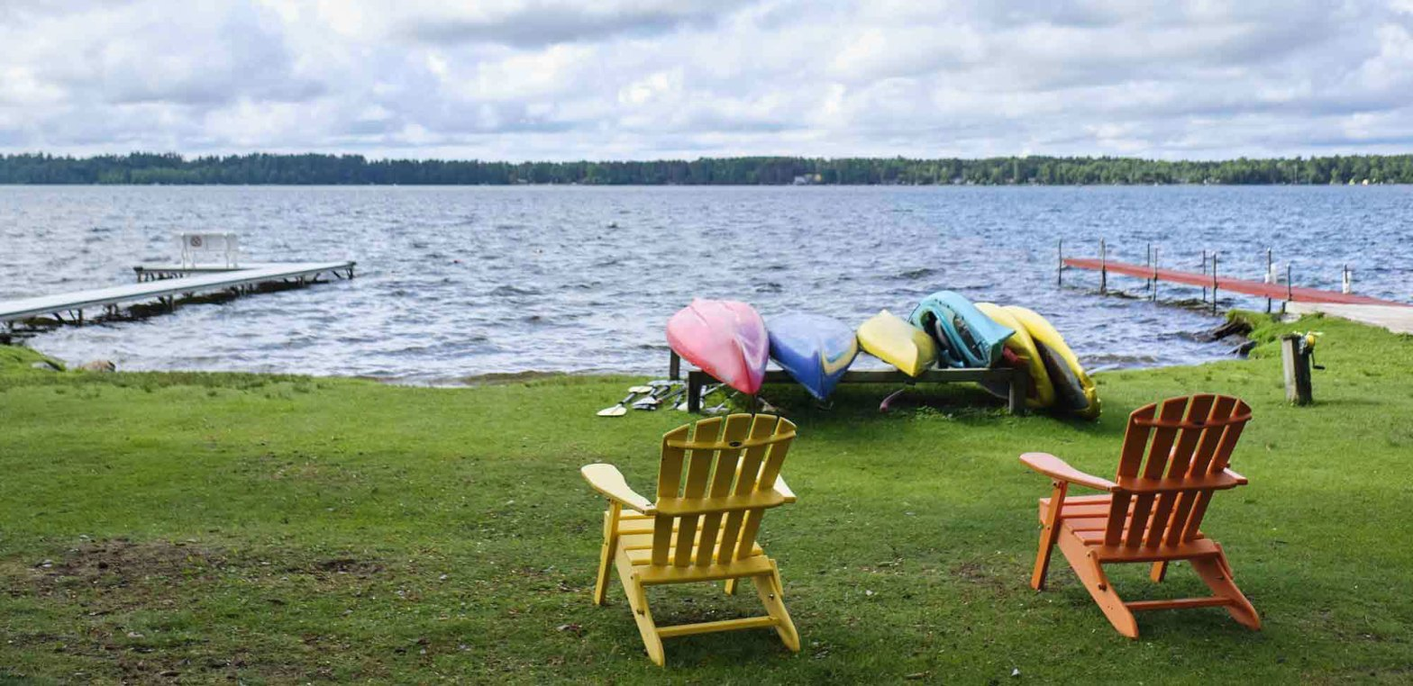 lake with Kayaks and Adirondack chairs on a sunny day