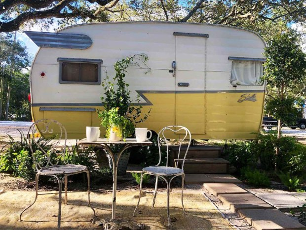 A yellow vintage Shasta camping trailer camping with chairs and table on a sunny day