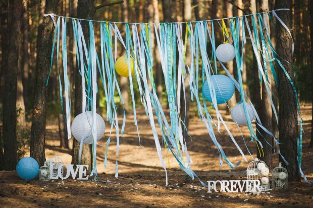 valentines day streamer photo backdrop hanging from trees with balloons