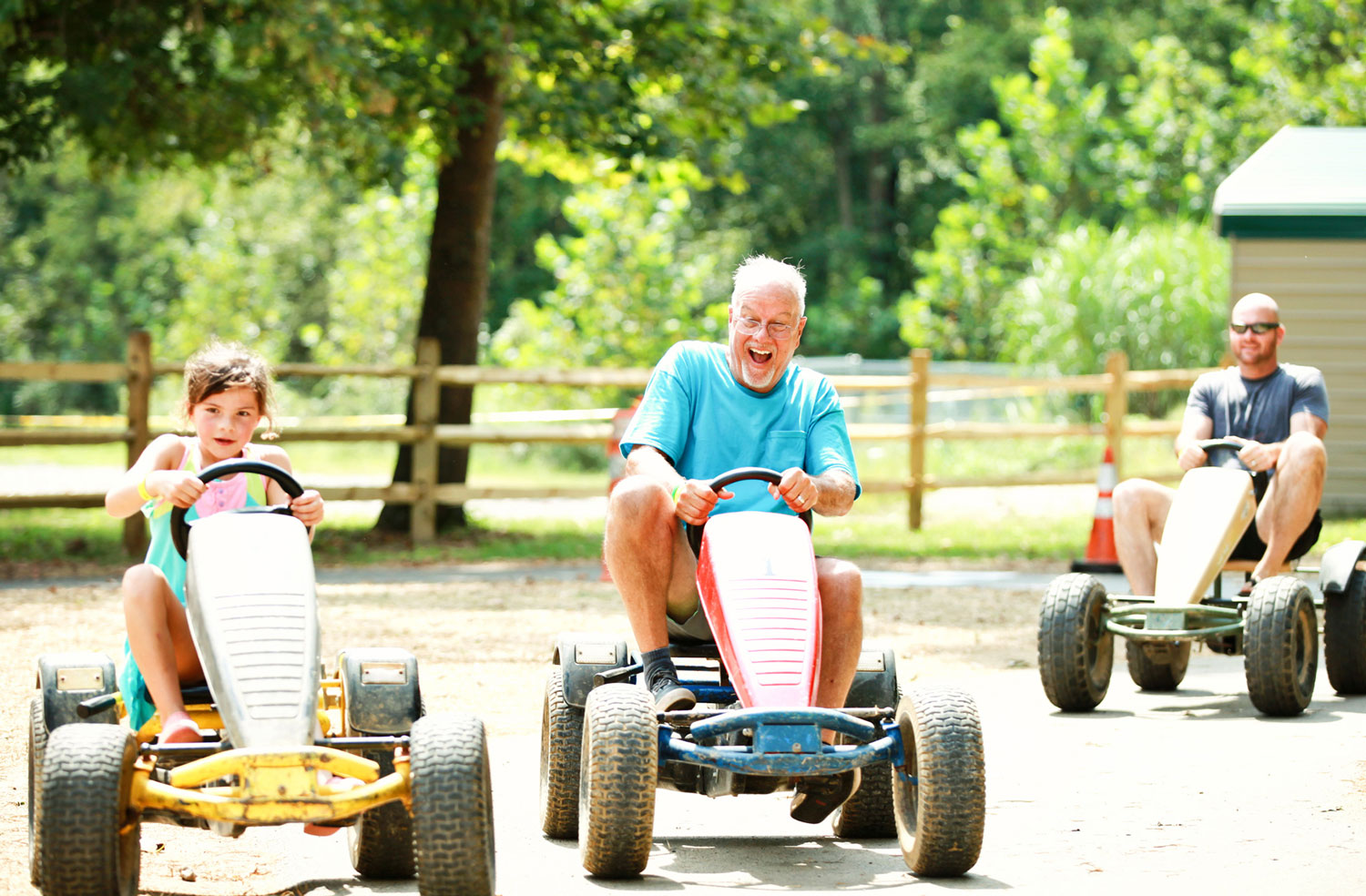 father and daughter on campground pedal carts on racetrack