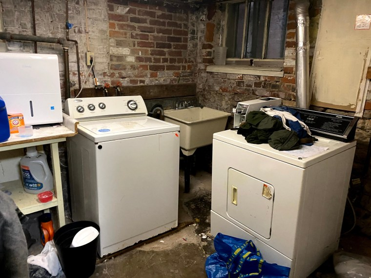 A basement room with a laundry machine and laundry dryer