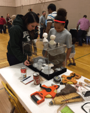 Amy explains artifacts to an elementary school student.