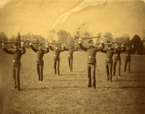 1886 image of officer candidates drilling with firearms on Adams Field.