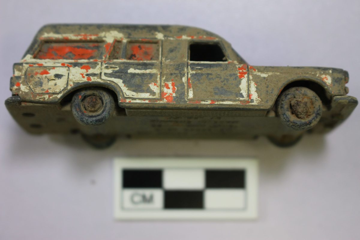 A dirty, red and white painted metal toy car.