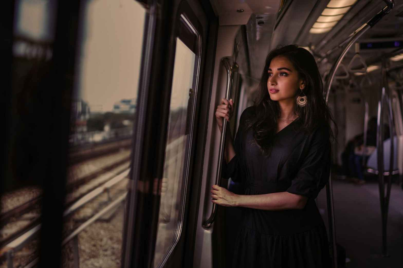 photo of woman standing inside train holding on metal rail while looking outside