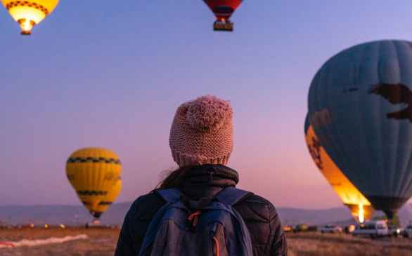 back view of a person carrying a backpack while watching the hot air balloons