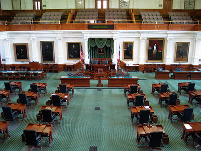 Empty leather chairs and desks dot the green carpet of the Senate chamber