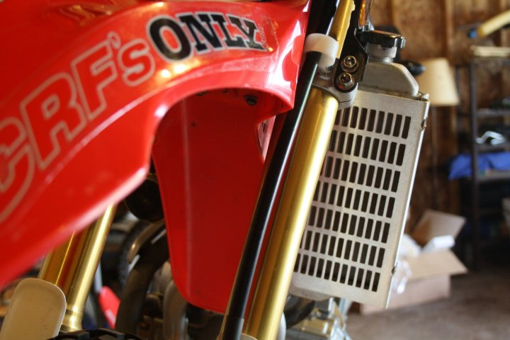 The Flatlands Racing rad guard is a much sturdier piece than the puny plastic guard Honda sends with the bike as stock.