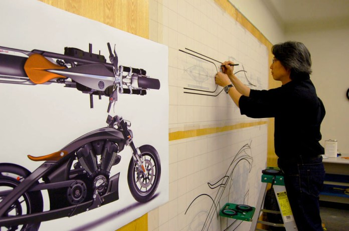 """Polaris designer Michael Song works on a full size """"tape"""" drawing of the Victory Core concept. Photo : Polaris"""