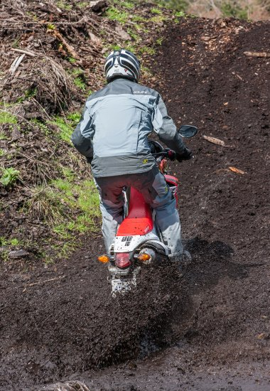 There's no stopping now. Launching the CRF250L through a muddy hole and up a slope in front of an expectant crowd of journalists