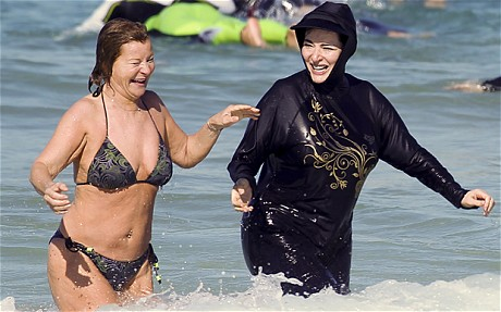 [A photo of Nigella Lawson in a black burqini cavorting in the surf with her friend Maria McErlane (who is wearing a bikini).]