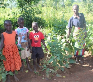 Mary smiles with her grandchildren in front of crops