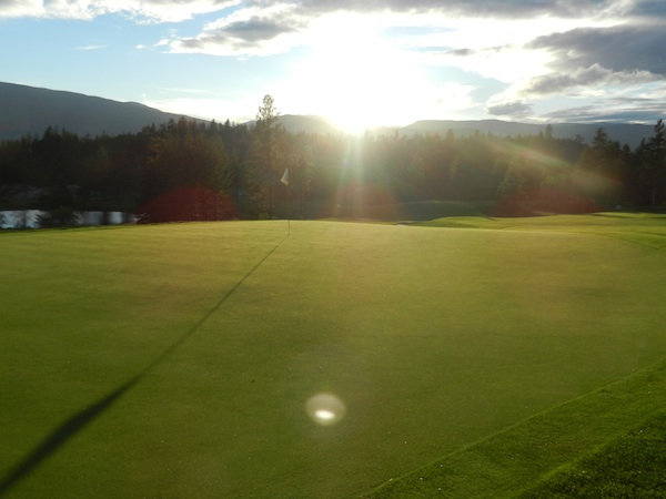 The 10th green as the sun sets behind the mountains.