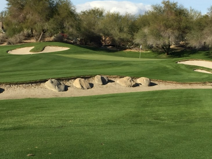 Small boulders stand guard in from of the open fronted green on the Par 17th