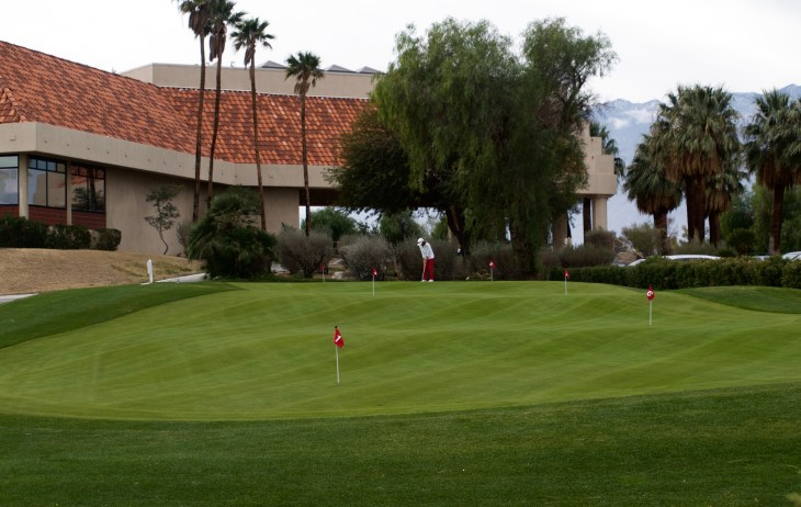 Desert Dunes Practice putting green with clubhouse in background