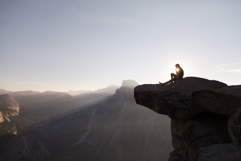 A man sitting on the top of a cliff