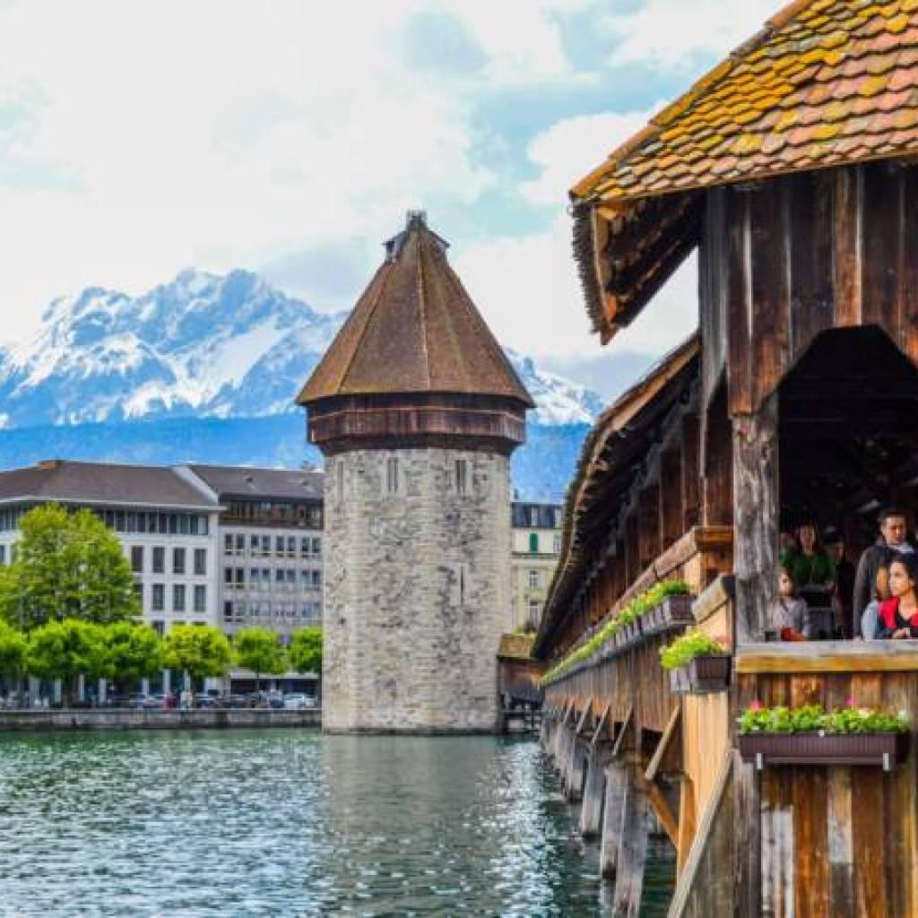 tourists walking on wooden bridge near medieval tower