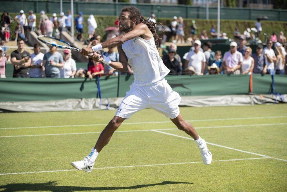 Dustin Brown golpea un revés en la face previa de Wimbledon