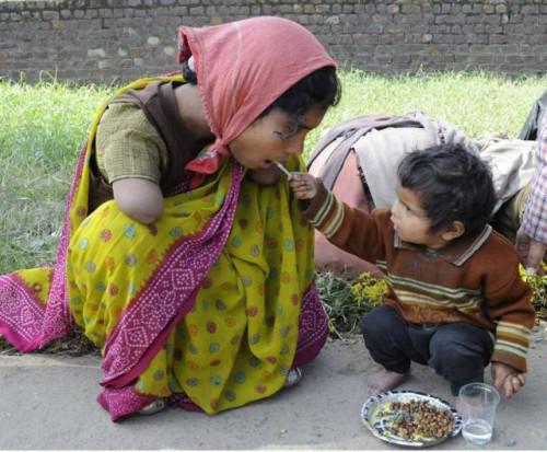 Nino de 2 anos dando de comer a su madre con discapacidad