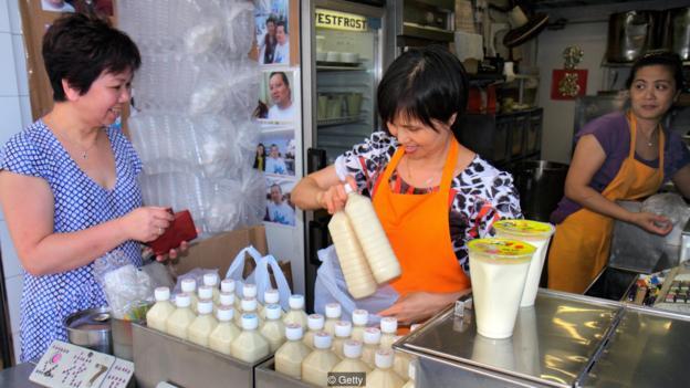 mujer comprando leche soja