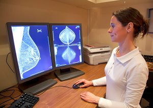 A radiology technician looking at a mammogram.