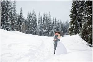 Bride and grrom standing in the snow hugging on their wedding day