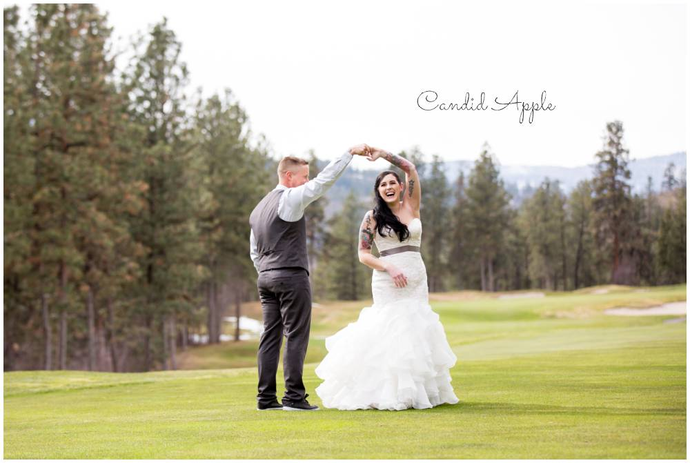 A birde and groom dancing on a golf course in the spring