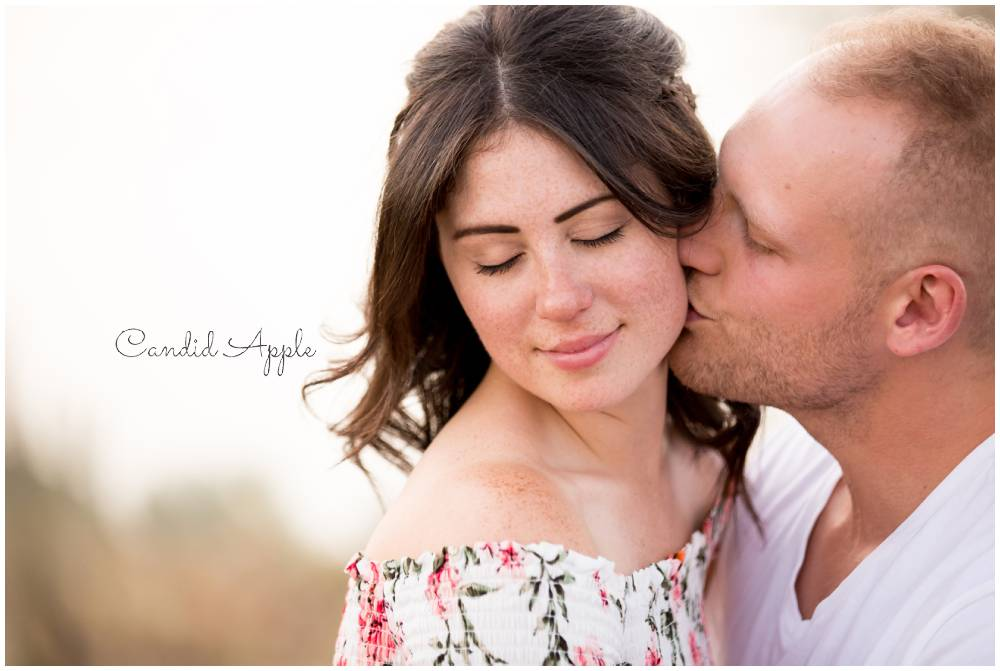 A couple snuggled up on a mountaintop During thier engagement session