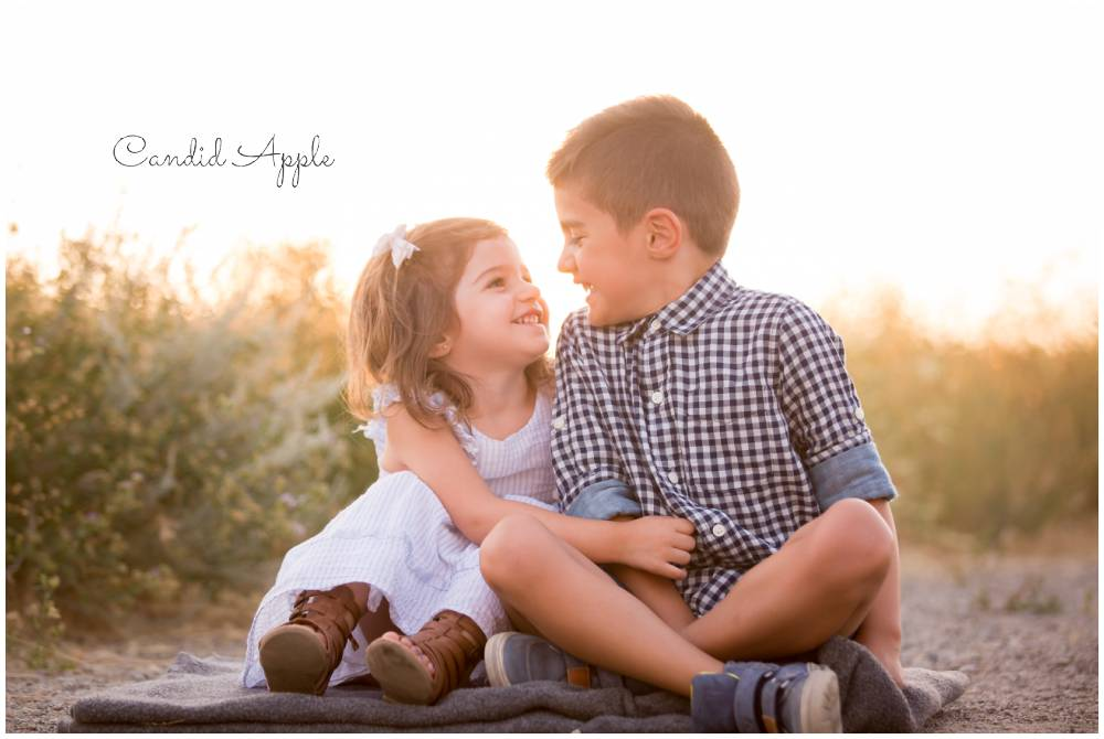 Two children looking at each other giggling at sunset