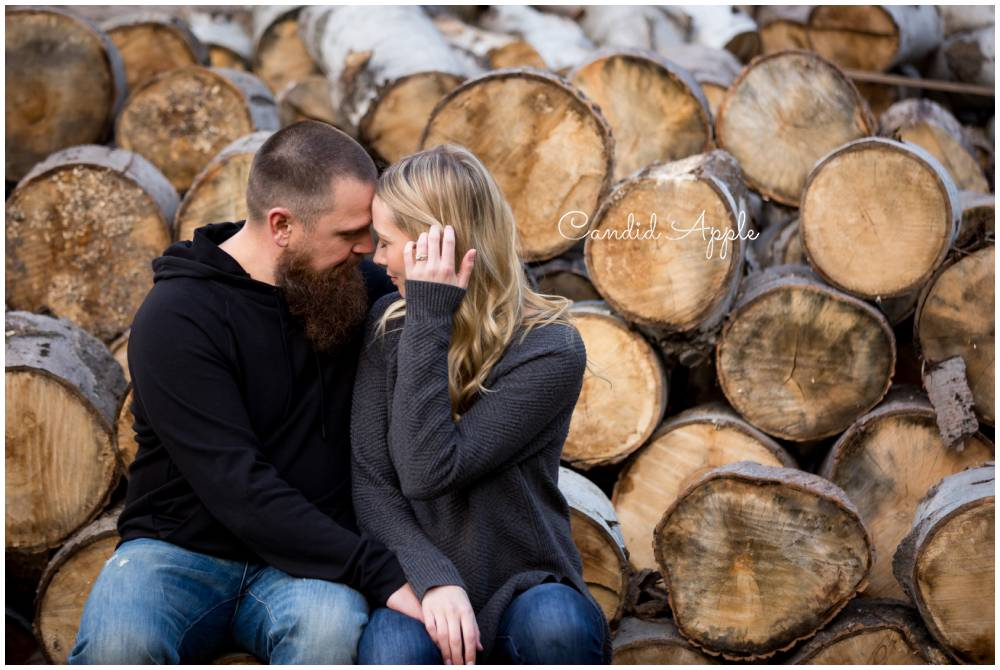 A couple snuggled up in front of a log pile