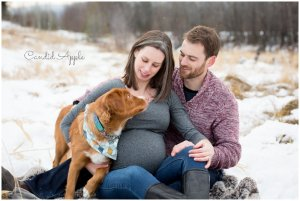 A family sitting in the snow with their puppy during a maternity session