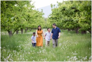 A family holding hands walking through an orchard