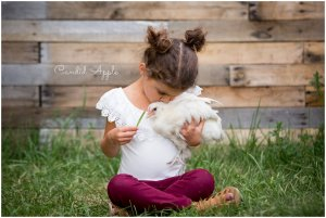 A little girl snuggled up with a chicken