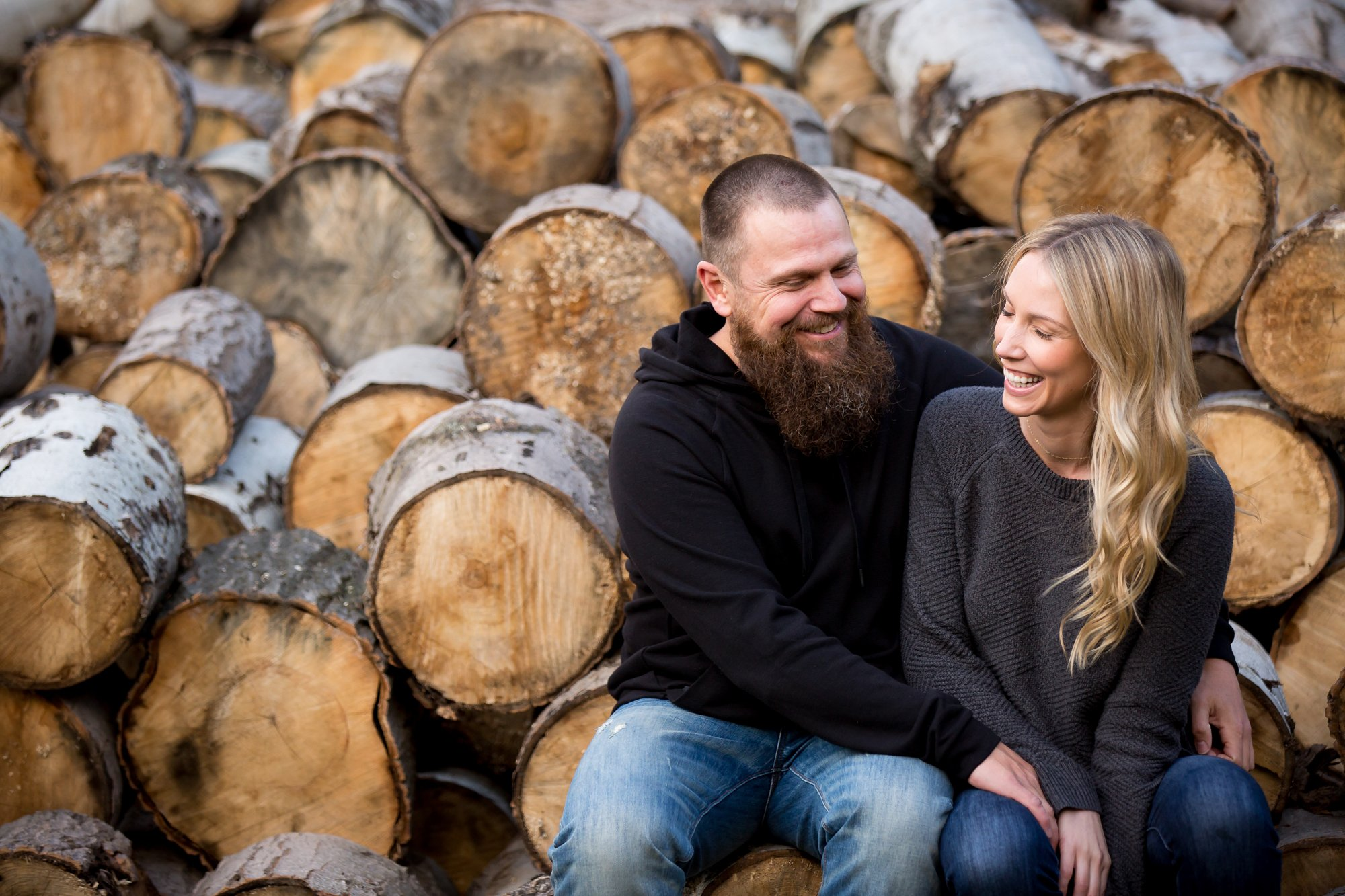 A couple laughing together on a log pile