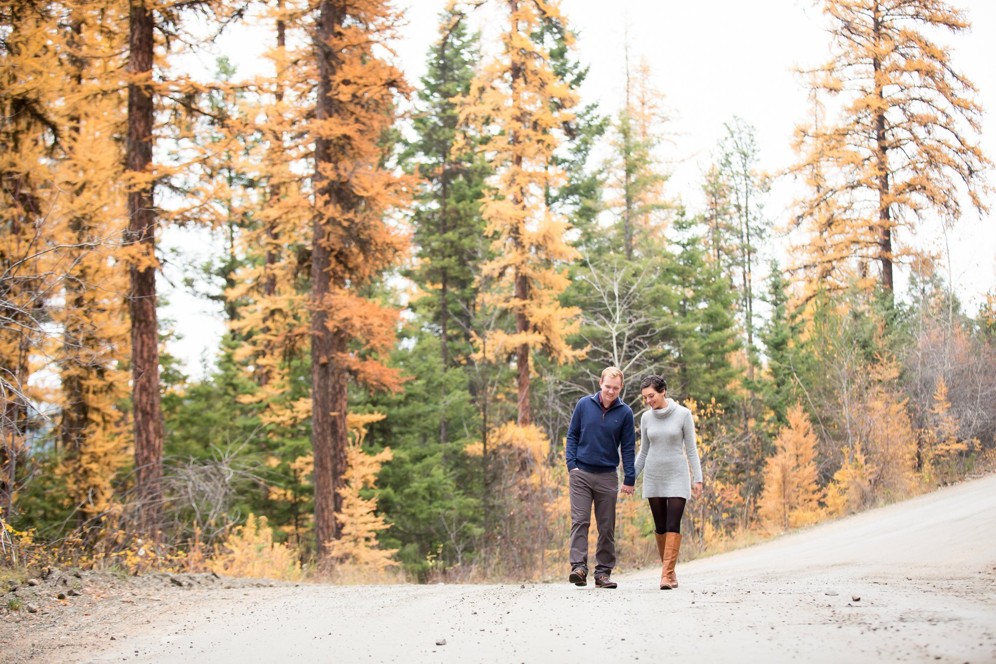 A couple walking hand in hand in the fall trees