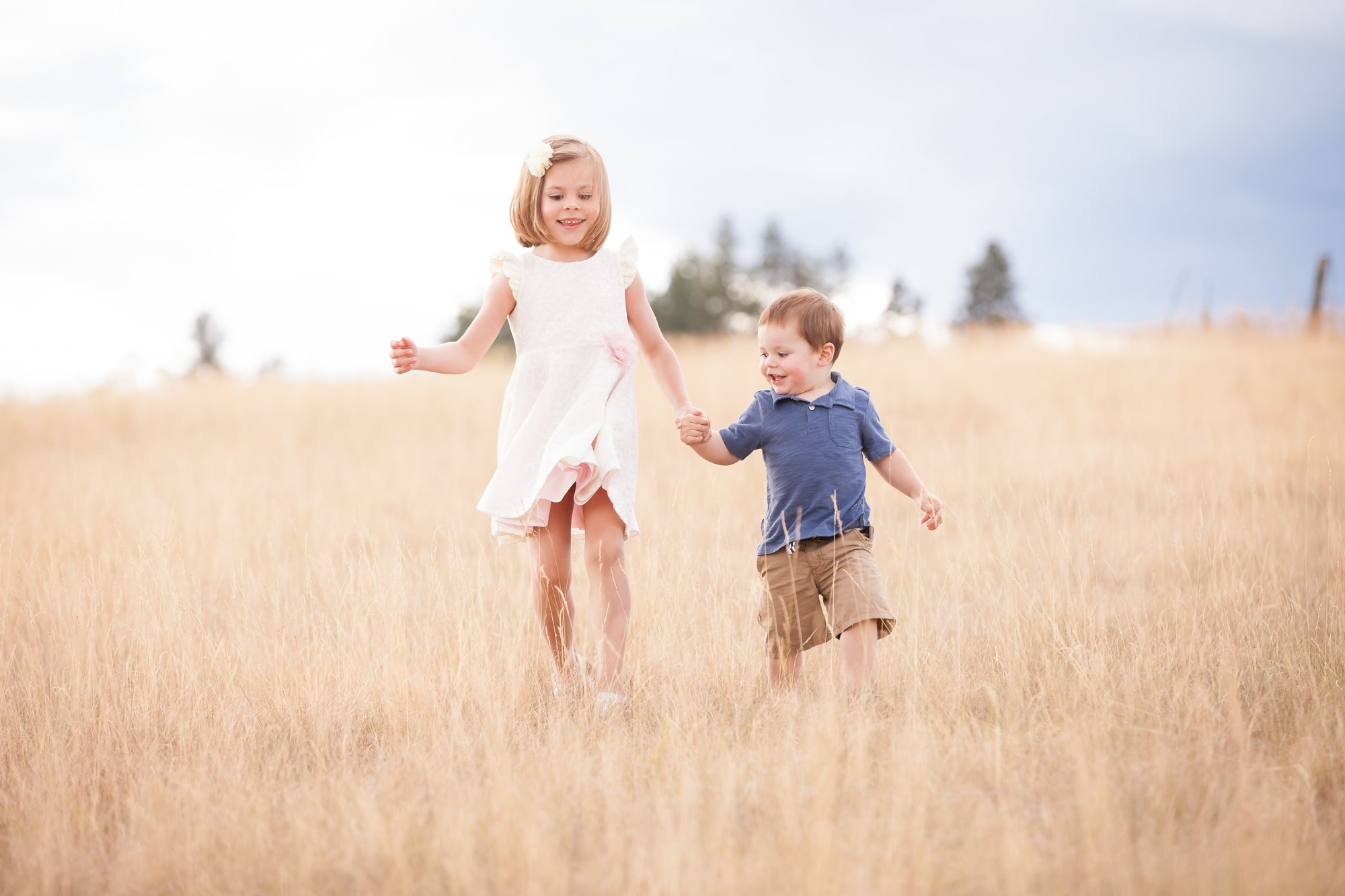 A brother and sister running hand in hand in the long grass
