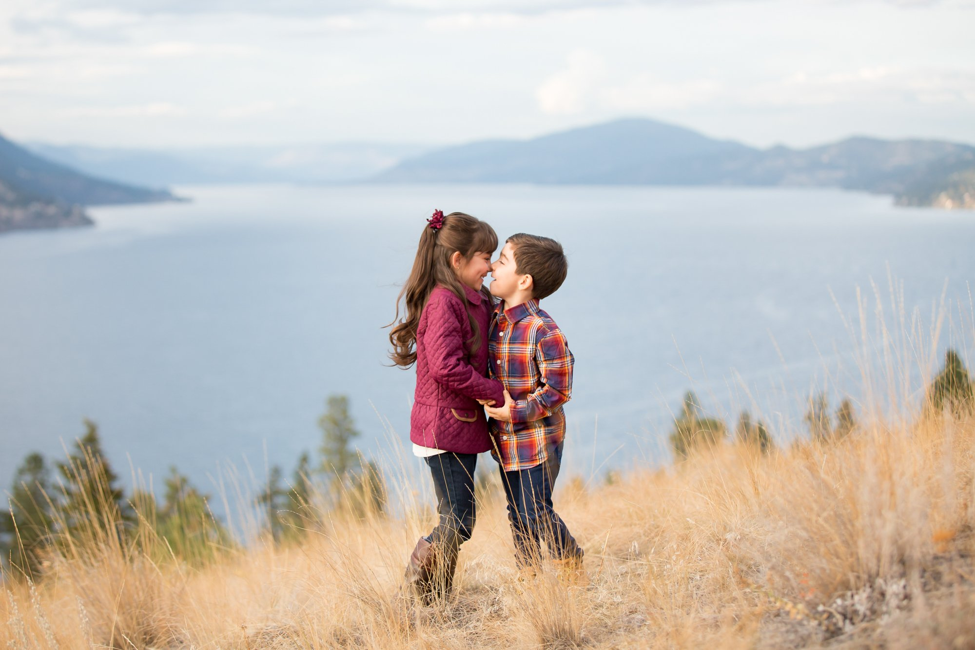 Siblings touching noses together in a field overlooking the lake