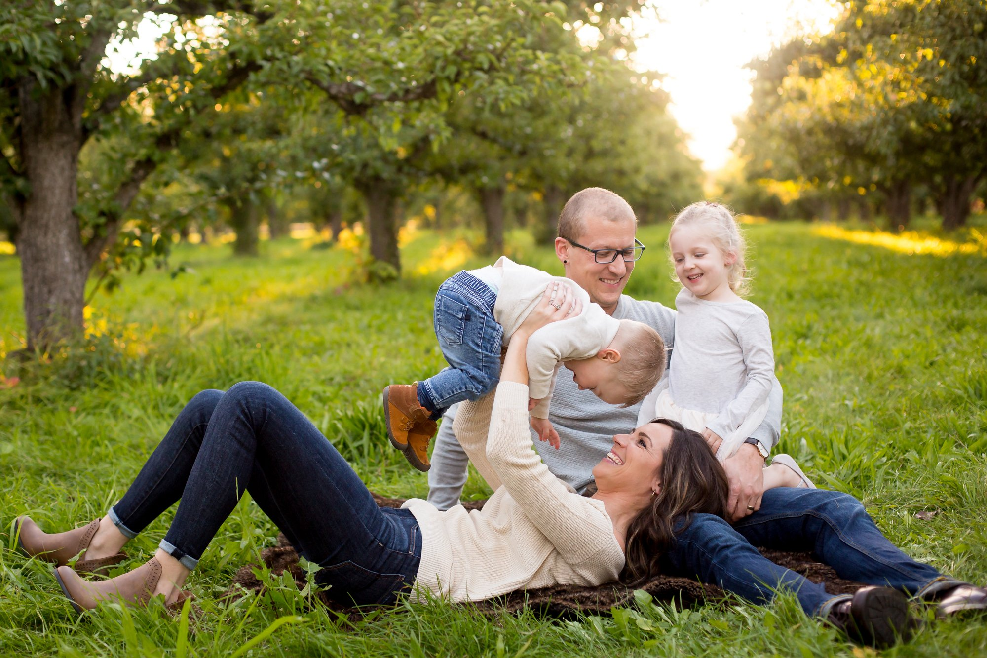 A family playing in an orchard