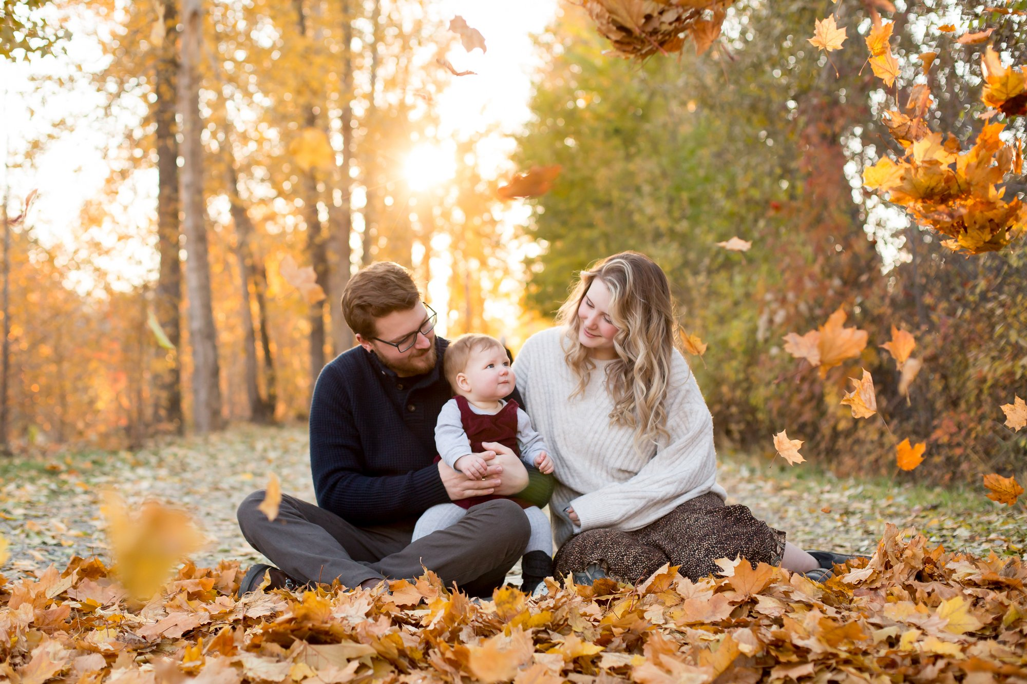 A family sitting in all the fall leaves