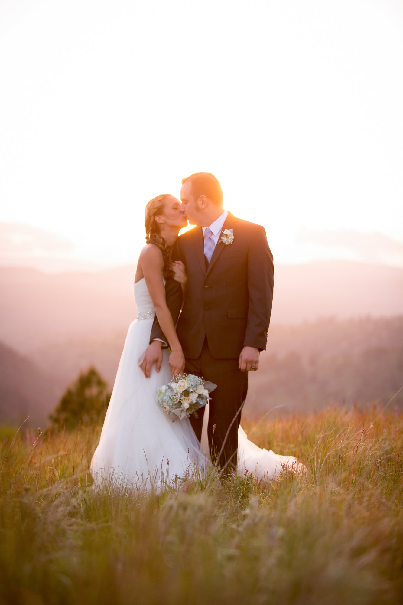 A bride and groom kissing on a mountain top