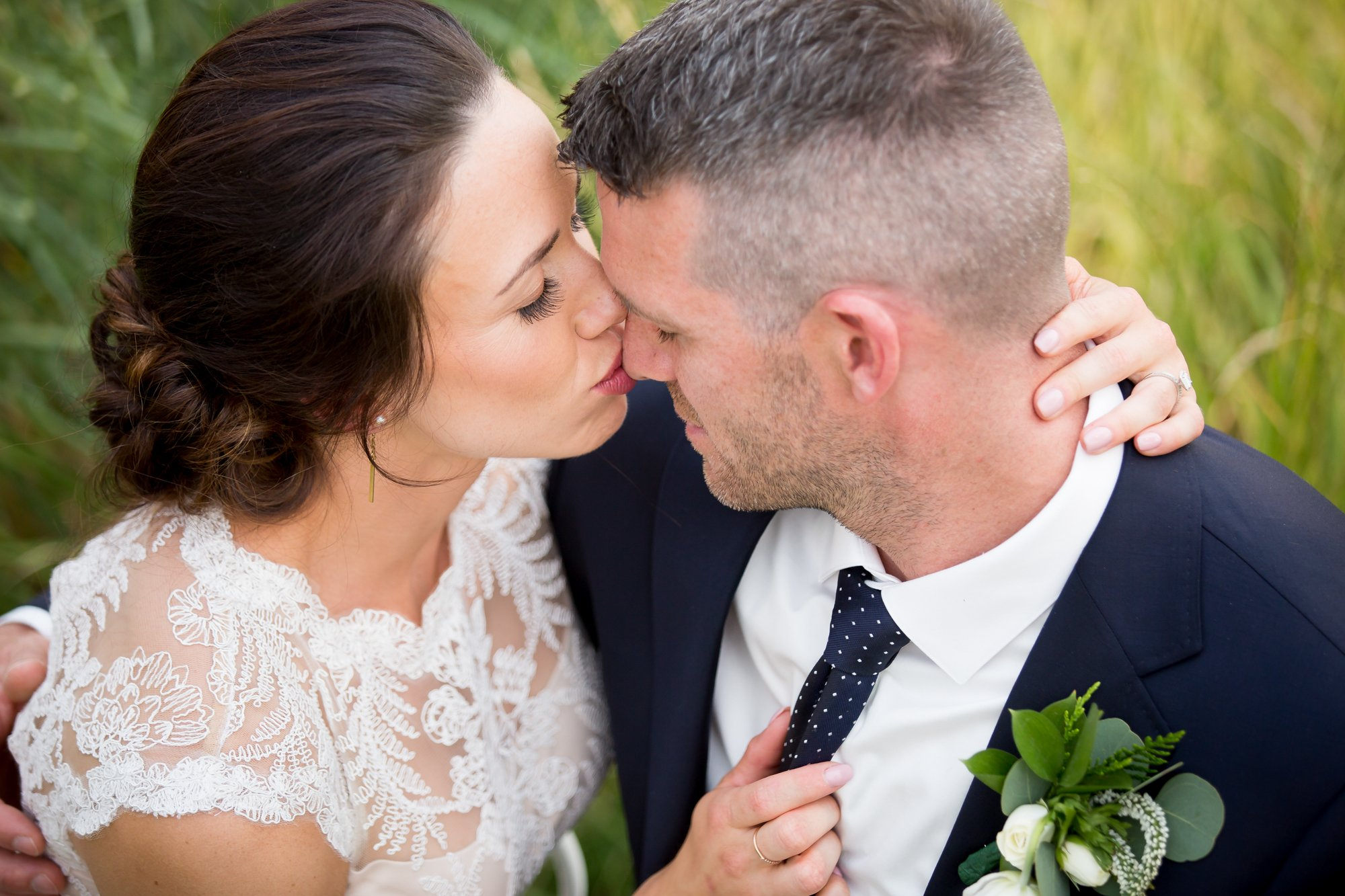 a bride kissing her groom on the nose