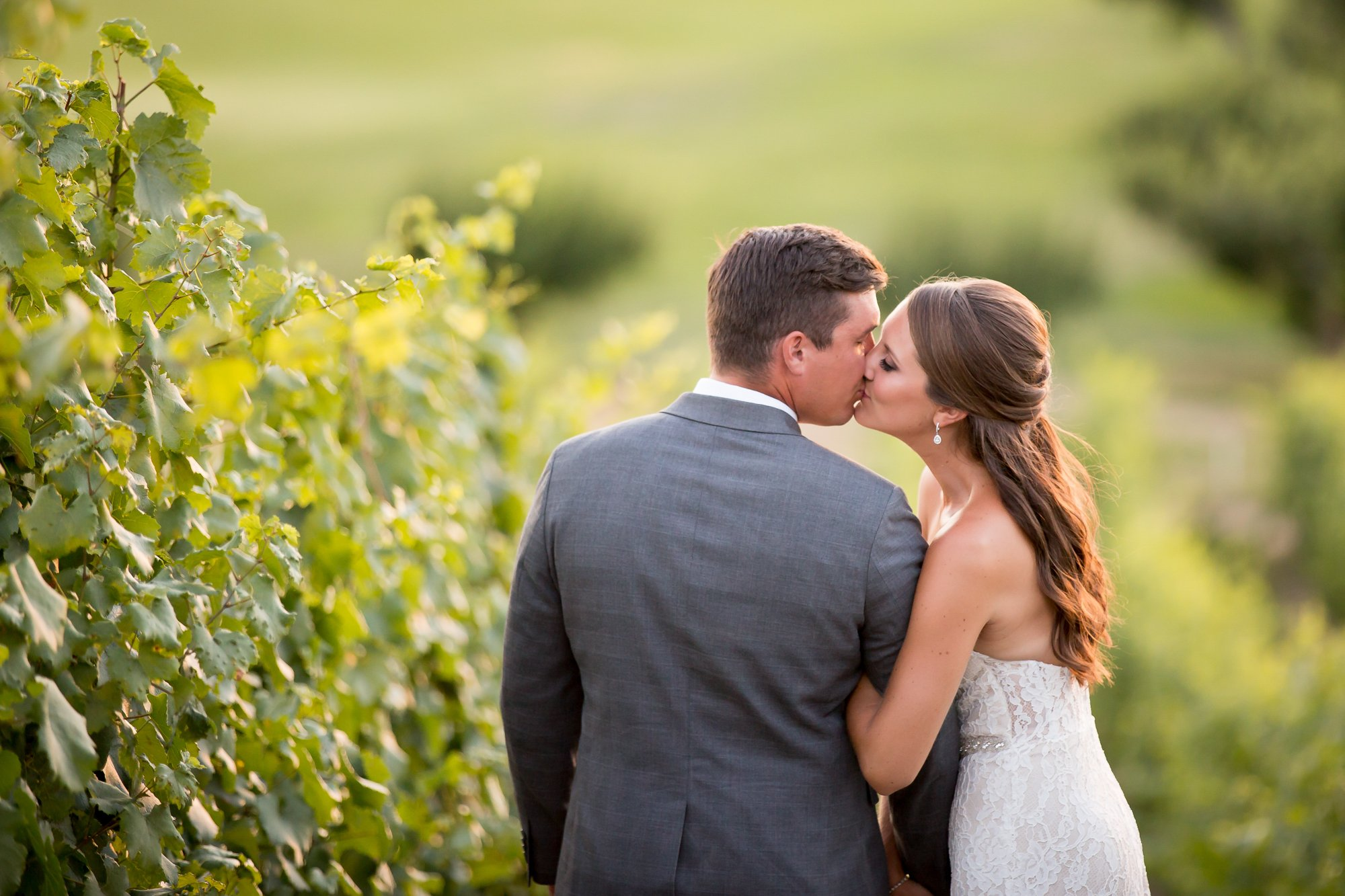 A couple kissing drung the golden hour in a vineyard