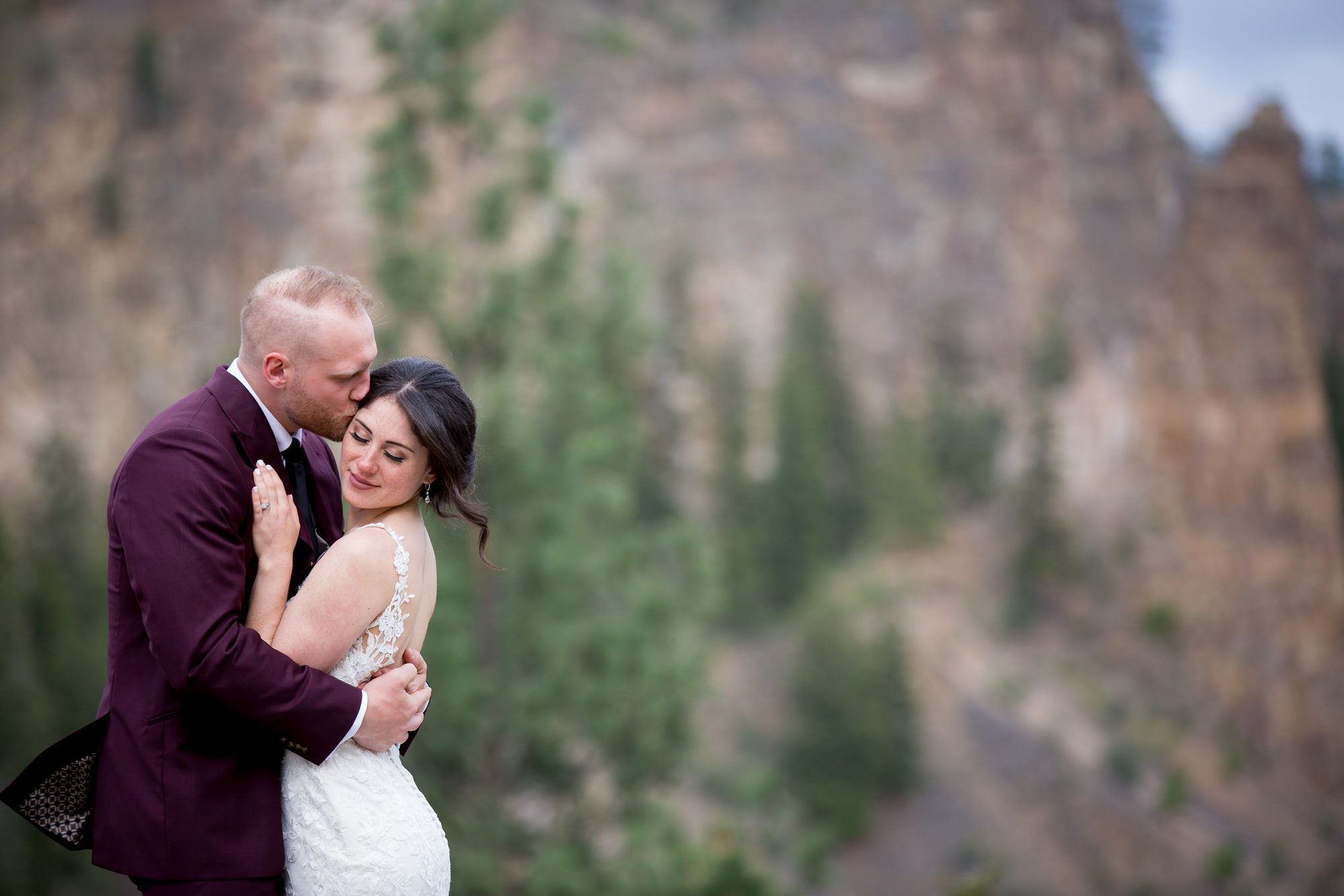 A groom kissing his bride in the wind