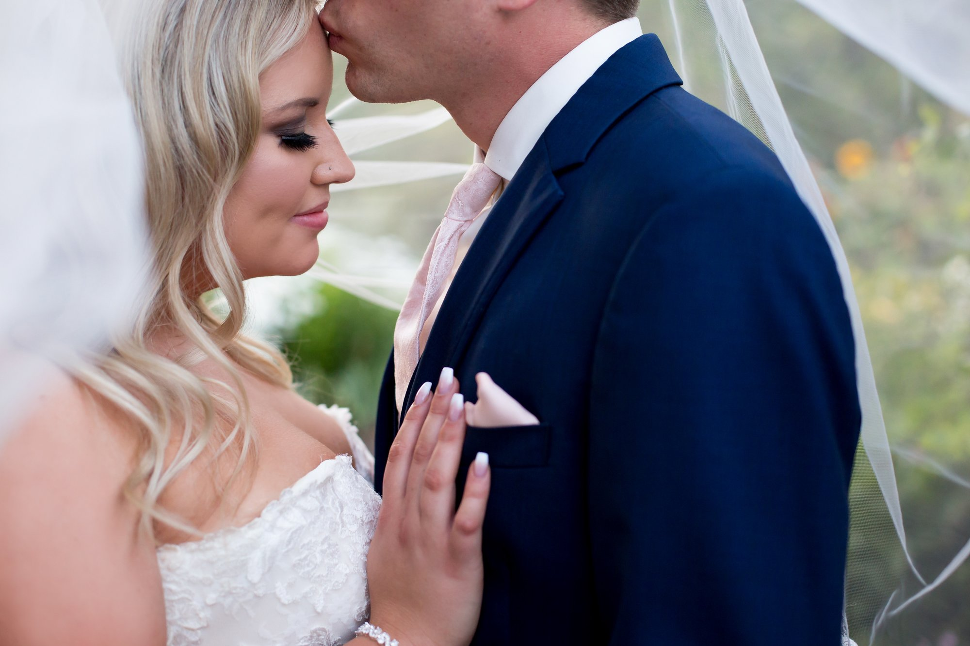 A groom kissing his bride's forehead