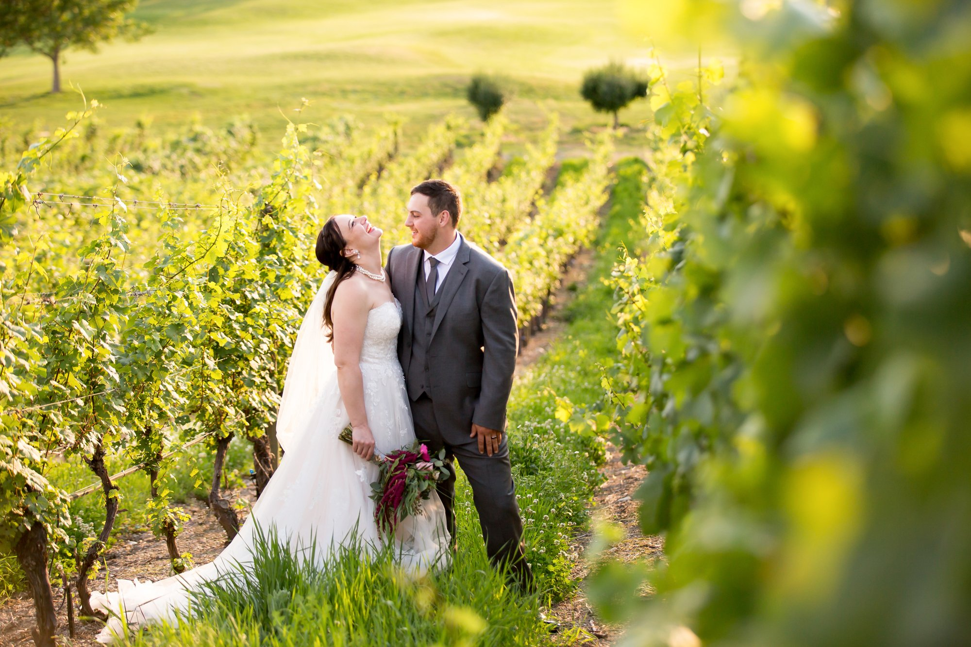 A couple laughing together in a vineyard