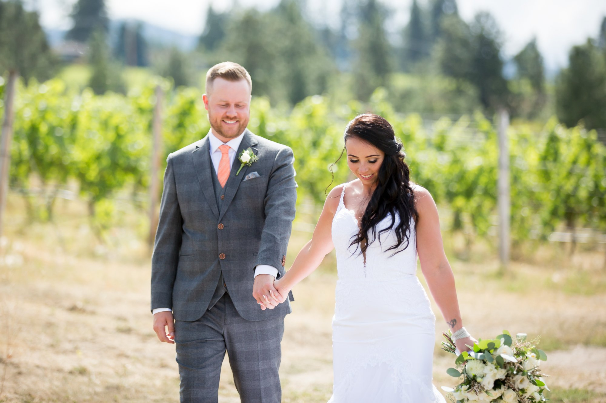 A couple holding hands in a vineyard