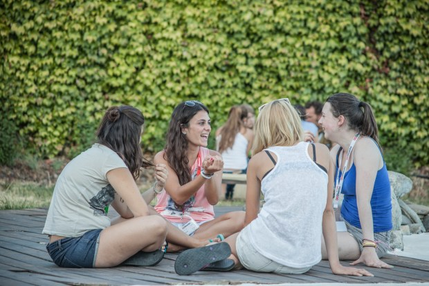 Teen girls sitting on the ground having a conversation.