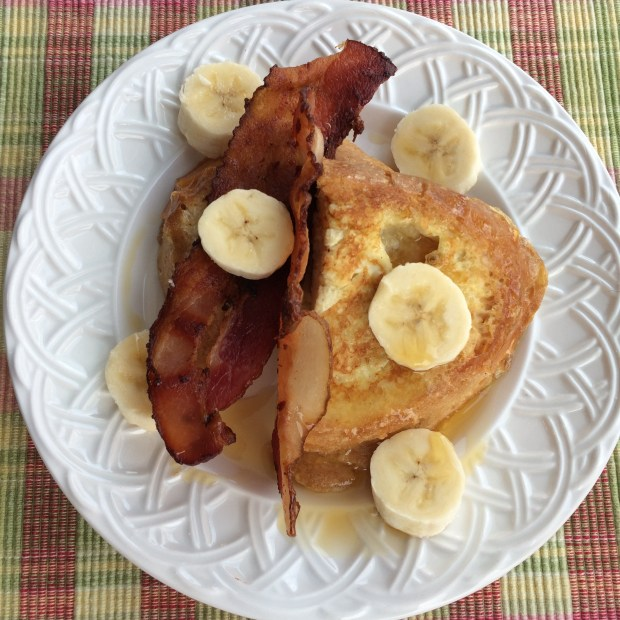 french toast on a white plate with bacon and banana